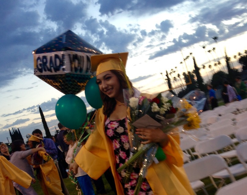 young lady in graduation cap and gown, holding balloons